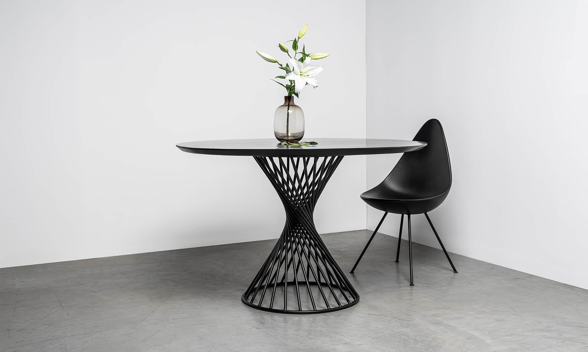 Okrągły stół z czarnym blatem na prętach spirala. Stół Oliver od Hoom
